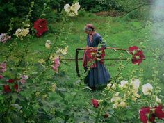 She is captured here carrying the scythe that she used in her gardening..