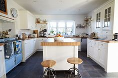 Mid century modern kitchen with white cabinets, light wood counters and vintage blue oven