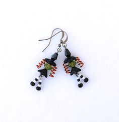 Enjoy some spooky Halloween fun wearing these whimsical witch earrings. Created with glass, crystal and plastic beads for her hat, head, skirt, sox and feet, and orange copper wire spiraled for her long curly hair, they are secured with gun metal fish hook ear wires. While her legs dance with wicked glee, her witch hat shimmers mysteriously in the light and they measure a supernatural 2 long from the top of the ear wire. Happy Halloween! Thanks for stopping by connectionsbymaya and for…