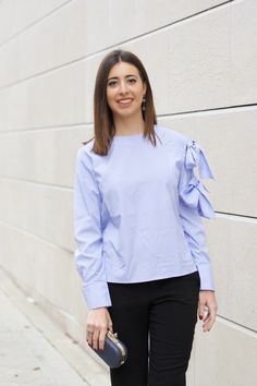 midilema.com | Christmas dinner | Lucía Peris is wearing feminine blue shirt with a blow ties sleeve, classic black pants, fuchsia high heels, and blue clutch with golden details for a special occasion. Events. // Lucía Peris lleva una camisa azul femenina con lazos grandes en una manga, pantalones clásicos negros, tacones fucsias, y bolso de mano azul con detalles dorados para una ocasión especial. Eventos.