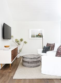TV seating area in bedroom: Textured ottoman and rug, bright white chairs, and entertainment unit with walnut.