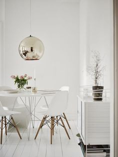 At first, take a look at this beautiful white dining room round dining table matches the iconic Eames dining chairs and gold pendant lamp string shelves roses.➤ Discover the season's newest designs and inspirations. Visit us at www.moderndiningtables.net #diningtables #homedecorideas #diningroomideas @ModDiningTables