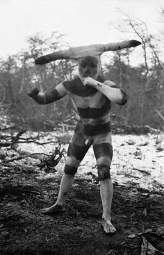 The spirit Halahaches is a horned and clown-­like figure. He visits the camp every day during Hain, the Selk'nam initiation rite, and tries to scare the women.  Photo by Martin Gusinde, 1923.
