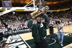 Le'Veon Bell holds up the Elite Running Back Trophy to the crowd at halftime of the men's basketball game.