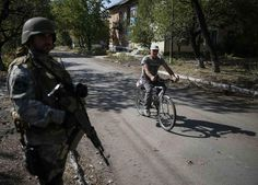 civilian bike usage in Ukraine: A Ukrainian paratrooper stands guard as a local resident rides on a bicycle near Zhdanivka September 13, 2014