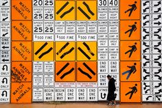 A pedestrian walks past a mural on the side of a building made from more than 500 highway signs in Phoenix,