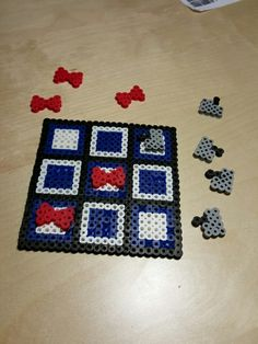 Perler tic-tac-toe with Doctor Who theme. TARDIS colors for the board, bowties and grey Daleks for pieces.