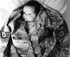 baby in dads military uniform