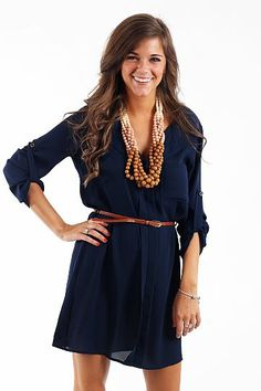 "Easy Shirt Dress, Navy $41.00 Another great dress that is modest and professional looking! This dress is perfect for work or school; we love the small collar, buttoned up sleeves, and the belt that comes with it! This number is a bit sheer, you may want to wear a layering tank or a slip!   Fits true to size. Miranda is wearing a small.   From shoulder to hem:  Small- 33""  Medium- 34""  Large- 35"""