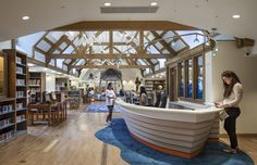 This information desk in the Children's Reading Room at the East Hampton Public Library is shaped like a fishing dory and references the heritage of Long Island's East End | Interior design & environmental graphics by LHSA+DP | Architect: RAMSA | Photography byFrancis Dzikowski/OTTO #fishing dory #boat #reception #information desk #aquatic #nautical #long island #hamptons #children's library #public library