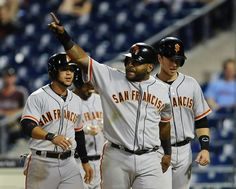 San Francisco Giants' Pablo Sandoval, middle, walks off the field with Buster Posey, right, and Gregor Blanco after they scored on a Brandon Crawford double in the fourteenth inning of a baseball game on Wednesday, July 23, 2014, in Philadelphia. The Giants beat the Phillies 9-6 in extra innings. (AP Photo/Michael Perez)
