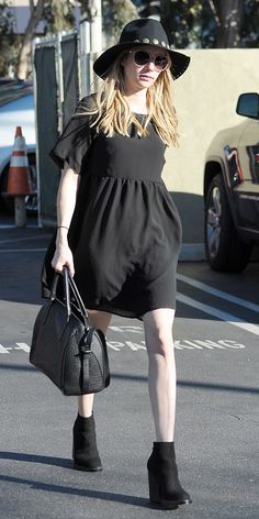 Emma Roberts goes for an edgy boho look in a LBD, floppy hat and chunky black ankle boots