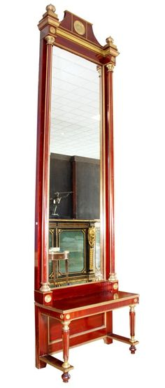 EMPIRE MAHOGANY PIER MIRROR:    A palatial Empire style mahogany pier mirror consisting of a tall vertical beveled mirror flanked by two projecting columns with gilt recesses, topped with gilt urns. All resting on a low console table supported by columns connected to the projecting stretcher legs.
