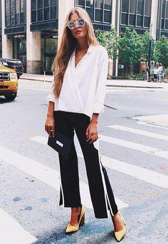 Teresa Andrés usa calça alfaiataria com recortes laterais, camisa branca com decote transpassado e scarpin amarelo.
