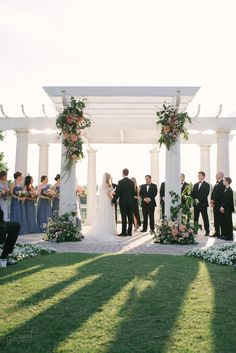 wedding ceremony at the elegant ritz carlton lakeside gazebo featured grand columns dressed with lush cascading organic arrangements of coral, pink, peach, blush, ivory and white flowers, vines, branches and greenery.