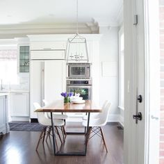 Eat-in kitchen boasts Eames Molded Plastic Chairs flanking an iron and wood modern industrial dining table illuminated by a nickel lantern.