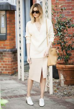 A v-neck sweater is worn with a beige slit skirt, white oxfords, and a tan leather bucket bag