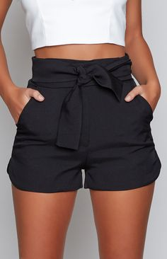 High waisted black shorts have never looked as good as the Bow Peep Shorts Black. Featuring two long fabric ties with holes to thread through, creating a wrap around look on your waist! These shorts also feature a zipper opening, two pockets on the side and curved open hem on the side of the shorts. Style these shorts with simple tees to show off the tie up waist and a pair of black boots! FABRICATION: 100% Polyester SIZE & FIT: Measures: 36cm from neckline to hem Model's Height: 1...