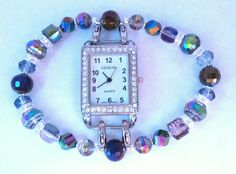 Rectangular white watch face is surrounded with rhinestones.  The band features a variety of wine- colored iridescent glass beads and clear crystal rondelles.