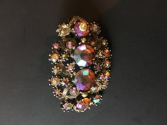 1960s Aurora Borealis Brooch , £10.99 by lovelyglo:  Beautiful Aurora Borealis Brooch. one tiny mark on one of the central stones but can't be seen directly. Four large central stones 2 measuring 1.5cm circular, 2 x 1.com and then surrounded by 20 or so smaller stones.  Total Size 7cm x 5cm