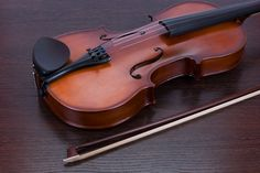 classic violin closeup - classic violin closeup on a brown wooden background