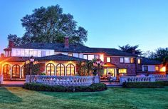 This 'Gatsby Lane' home in Great Neck, NY has brick facade, arched openings, black trim, slate shingle roof, multiple chimneys, stone railings, a large patio, and elegant outdoor furniture.