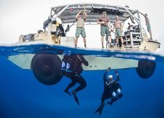 Seabee Divers, with Underwater Construction Team 2 Construction Dive Detachment Bravo (UCT2 CDDB), performing maintenance on undersea cables at the Pacific Missile Range Facility Barking Sands, Hawaii, surface near their Lighter, Amphibious Resupply, Cargo, 5 ton (LARC-V).