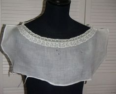 "Tucker (worn under wide/deep necklines, in day or evening) from England, sold on ebay. ""It is made of a fine cotton fabric with a delicate band of whitework embroidery all round the neck, edged with bobbin lace.  The whitework is very finely done, in a continuous design of tiny  flower sprays and leaves... the back [and front] from the neck edge to hem is 9 1/2 inches... The shoulder seam measures 3 inches ... as the neck is very wide.  The side seams are finished with a hand  stitched hem."""