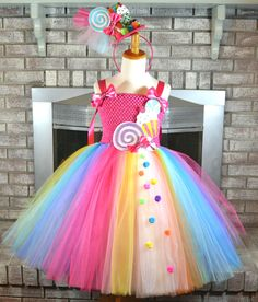 Check out this super SWEET Candy Land Tutu Dress! It comes with the matching top hat headband. This is meant to be at knee length or slightly below. Materials used: Glitter, Foam, Felt, Wood (for lollipop stick in headband only), trim, tulle, rhinestones, ribbon and felt were all