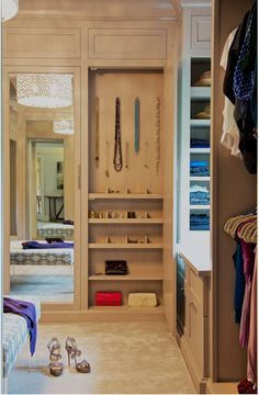 Stunning walk-in closet with built-in, tan colored cabinets with mirrored doors reflecting an Oly Studio Meri Drum Chandelier over a blue geometric ottoman with an open closet to the right featuring built-in jewelry hooks and shelves. Beautiful Closets, Front Closet, Interior, Home, Walk In Closet, Closet Vanity, Build A Closet, Interior Design, Cabinet Colors