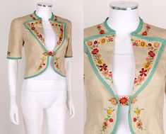 Short sleeves. Wide lapels held open by two wooden buttons. Embroidery on neckline, sleeve, lapel, hemline, and button band. Edges bound in teal bias tape. Heart shaped patch pocket on left chest.   eBay!