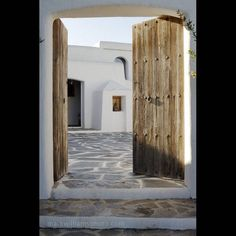 Entrance to house on Greek Island: I wish for an entrance like this, I like it when its quite simple! Of course I would love to paint the wooden gate in a fun color like red, blue or yellow. Style Ibiza, Spanish Courtyard, Myconos, Flagstone Flooring, Old Doors, Stone Houses, Menorca, Mediterranean Style, Future House