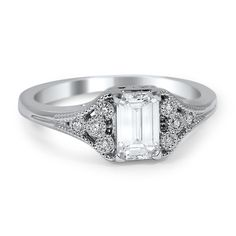 An emerald cut diamond is elegantly framed with bezel set diamond accents and lined in delicate milgrain in this excellent engagement ring.