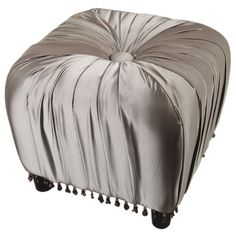 Perfect pulled up to your vanity or cornered in a powder room, this chic tufted ottoman in silver showcases pleated upholstery and tassel fringe.