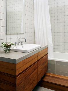 Banheiro branco com gabinete em madeira.