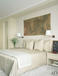 In the master suite, a painting by Olga de Amaral is displayed above a bed dressed in a Larsen silk with a Pratesi cashmere blanket.