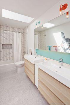 This modern kids bathroom has a skylight, colorful lamps, backsplash and towel racks, and a fun animal mural on the wall. #KidsBathroom #BathroomDesign #ModernBathroom