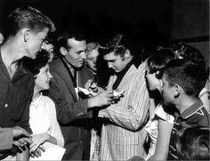 """Elvis and Carl Perkins exchanging autographs. On May 1, 1956 Elvis made a surprise visit to the Overton Park Shell in Memphis. Johnny Cash, Carl Perkins, Roy Orbison and Warren Smith were performing there but Elvis did not perform.  Photo © Alfred Wertheimer 