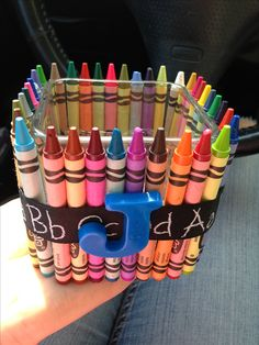 DIY teacher gift. $1 glass candle holder, hot glue crayons, tie ribbon. $1 pack of magnetic alphabets from michaels. Teachers initial.