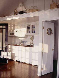 Designers decorated this cottage around a central, nautical theme. They added subtle accents, like a porthole window in the kitchen door, and seaworthy knickknacks along a high ledge. The result? A yachty interior that makes you feel like you're on the deck of a boat. (Photo: Photo: Deborah Whitlaw Llewellyn; Designer: Andrea Irvine and Rosselle Johnson) Beach Cottage Style, Coastal Cottage, Beach House Decor, Coastal Living, Coastal Decor, Coastal Entryway, Beach Condo, Coastal Furniture, Cozy Cottage