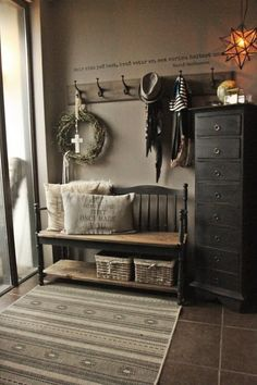 entry with bench (baskets on lower shelf), tall chest holds gloves, hats, etc. hooks, washable rug over tile, modern country farmhouse w/ industrial touches in Iceland, c. 2017