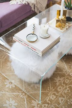 Loving the clear coffee table, poofs that peek through underneath and candle holders...plus, that RUG!