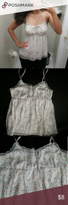Cute Lacy Detailed Top Tank top like blouse, sinches under chest for a baby doll look, lacey detailing, little blue, black and pink flowers Ive had this for a while and it still looks great.  Note: slight pink pigment shown on on chest area shown in the pictures Shell: 100% polyester Lining: 100% polyester Candie's Tops