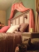 Old Door Headboard w old light sconces, Wire basket upside down w curtains slipped over wire curls