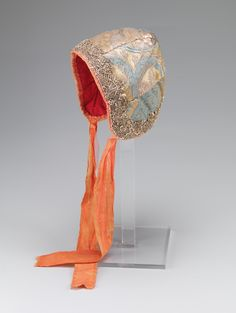 Infant's christening bonnet, Norway, 1700-1730. Silk brocade with a design of large floral motifs in yellow, pink, silver and blue, edged with orange silk ribbon and metallic lace, red silk lining.