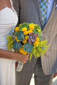 Mixed Succulent Bouquet.  Created with 22 succulents  in all different sizes in bright green and minty green and a touch of purple; yellow button poms and solidago as fillers. The stems are wrapped in natural fiber ribbon, twine, or white satin ribbon. <ul> 	<li> Bridal Bouquet measures approximately 10 inches in diameter. $185.00</li> </ul>