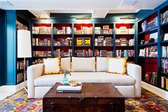 A cozy library with lots of color, neutral sofa, and built-in bookshelves