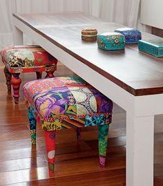 A mesa de jantar da casa da designer Ana Morelli tem banquinho revestido com tecidos de diferentes padrões