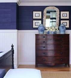 Loving the dark blue grasscloth, white beadboard with trim, and the rich colored dresser.  Great combo.