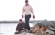 1085-John F. Kennedy Jr. (L), William Kennedy Smith (C) and J.F.K. Jr.'s dog Sampson (R) walk along a breakwater on the family compound in Hyannisport 23 January. The Kennedy family has gathered for Rose Kennedy's funeral who died 22 January at the age of 104. AFP PHOTO